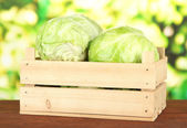 Green cabbage in wooden box, on bright background — Stock Photo