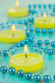 Lighted candles with beads on green background — Stock Photo