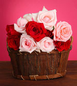 Beautiful bouquet of roses in wooden basket on table on pink background — Stock Photo