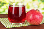 Glass of fresh garnet juice on table on bright background — Stock Photo