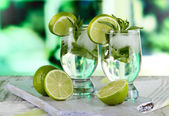 Glasses of cocktail with ice on board on napkin on wooden table on window background — Stock Photo
