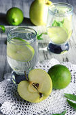 Glasses of cocktail with lime on napkin on light wooden table — Stock Photo