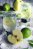 Verres de cocktail avec de la chaux sur la serviette sur la table en bois clair — Photo