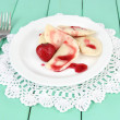 Tasty sweet dumplings with fresh strawberry on white plate, on color wooden background — Stock Photo #28090343