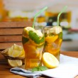 Iced tewith lemon and mint on wooden table, outdoors — Stock Photo #28091223