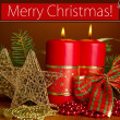 Two candles and Christmas decorations, on brown background — Stock Photo #28096379