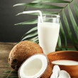 Coconut with glass of milk,  on wooden table, on grey background — Stock Photo