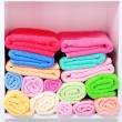 Colorful towels on shelves in bathroom — Stock Photo #28096467