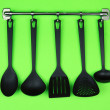Black kitchen utensils on silver hooks, on green background — Stock Photo #28096711
