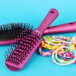 Scrunchies, hairbrush and hair - clip on blue background — Stock Photo #28097223