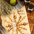Composition with old papers, herbs, stones and bottles with symbols on wooden background — Stockfoto