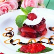 Tasty jelly dessert with fresh berries, on pink roses background — Foto Stock