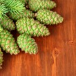 Green cones and fir tree on wooden background — Stock Photo #28099969