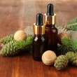 Bottles of fir tree oil and green cones on wooden background — Stock Photo