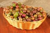 Fresh gooseberries in wicker basket on table close-up — Stock Photo