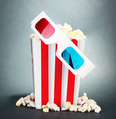 Popcorn and 3D glasses on grey background — Stock Photo