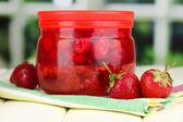 Domácí bobule marmeládou na dřevěný stůl na pozadí okna — Stock fotografie