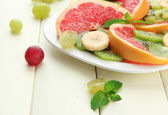 Sortiment krájeného ovoce na desku, na bílý dřevěný stůl — Stock fotografie