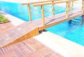 Bridge across hotel swimming pool — Stock Photo