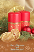 Two candles and Christmas decorations, on golden cloth background — Stock Photo