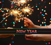 Beautiful sparklers in woman hands on garland background — Stock Photo