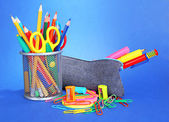 Pencil box with school equipment on blue background — Photo