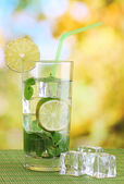 Vaso de agua con hielo, menta y limón en mesa sobre fondo brillante — Foto de Stock