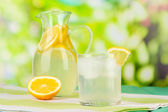 Citrus lemonade in pitcher and glasses on wooden table on natural background — Stock Photo