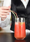 Barmen hand putting cocktail straw into glass, on bright background — Stock Photo