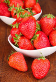 Fresh strawberry in bowl on wooden background — Stock Photo