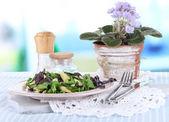 Light salad on plate on table on room background — Stock Photo