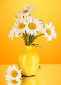 Beautiful bouquet chamomiles in vase on color background — Stock Photo