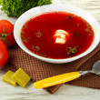 Bowl of soup with bouillon cubes on wooden table — Stock Photo #28101035