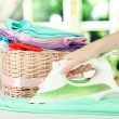 Stock Photo: Woman's hand ironing clothes, on bright background