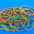 Colorful rubber bands on blue background — Stock Photo #28103567