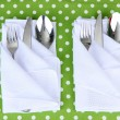 Stock Photo: Folded napkin with fork, spoon and knife on color background