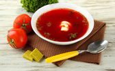 Bowl of soup with bouillon cubes on wooden table — Stock Photo