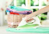 Woman's hand ironing clothes, on bright background — Stock Photo