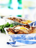 Food in boxes of foil on napkin on wooden board on room background — Stock Photo