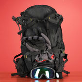 Winter sport glasses, helmet and gloves, backpack, on red background — Foto Stock