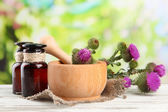 Medicine bottles and mortar with thistle flowers on nature background — Stock Photo