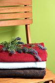 Asciugamani e fiori sulla sedia di legno su sfondo verde — Foto Stock