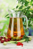 Pitcher of compote with summer berries on natural background — Stock Photo