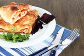 Pizza calzone auf platte auf serviette auf holztisch — Stockfoto