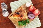 木製のテーブルにナプキンに木の板にピザ カルゾーネ — ストック写真