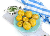 Boiled potatoes on platen on wooden board on napkin isolated on white — Stock Photo