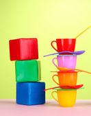 Conjunto de pratos para crianças e cubos na mesa sobre fundo verde claro — Fotografia Stock