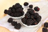 Sladký blackberry v miskách na dřevěný stůl — Stock fotografie