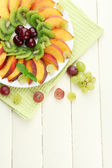 Assortment of sliced fruits on plate, on white wooden table — Stock Photo