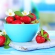 Ripe sweet strawberries in bowl on blue wooden table — Stock Photo